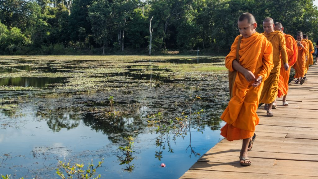 Monks on the walkway to Neak Pean, Cambodia